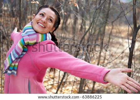 beautiful young woman enjoying her arms stretched out in the autumn park - stock photo