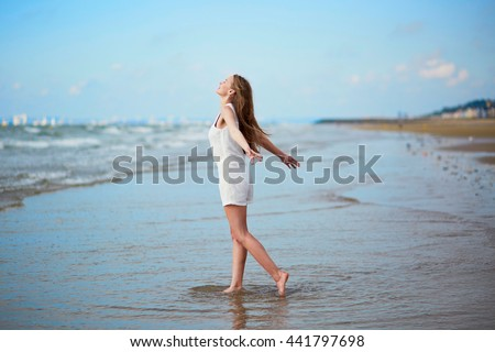 Beautiful young woman enjoying her vacation by ocean or sea, walking in water, arms wide spread. People on sea vacation concept