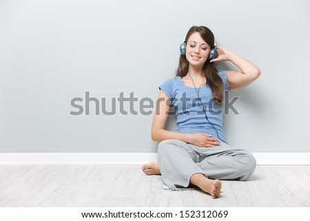 Beautiful young woman enjoying music through her headphones