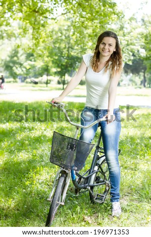 Beautiful young woman enjoying nature riding a bike.