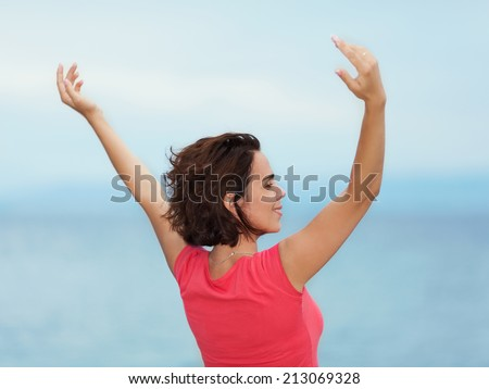 Beautiful young woman enjoying summer with her arms outstretched - stock photo