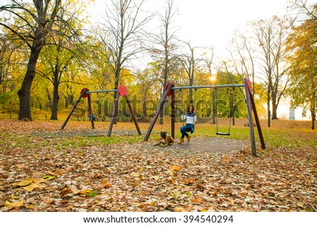 Beautiful young woman enjoying the autumn in the forest on a swing with her dog around. - stock photo