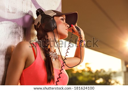 Beautiful young woman enjoying the music with headphones and wearing cap - stock photo