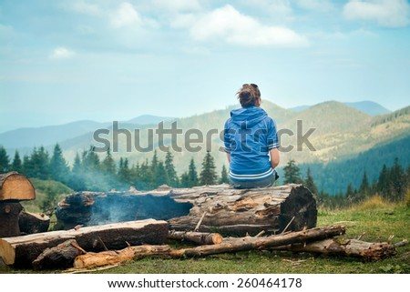 Beautiful young woman enjoying the nature and sitting on a tree trunk in the mountain - stock photo