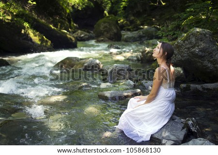 Beautiful young woman enjoying the pure waters of a mountain river in the forest