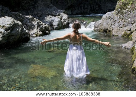 Beautiful young woman enjoying the purifying waters of a crystal clear mountain river