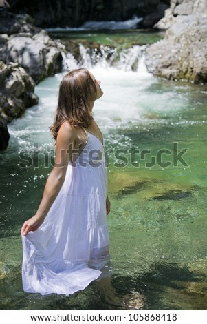 Beautiful young woman enjoying the purifying waters of a crystal clear mountain spring
