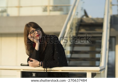 Beautiful young woman enjoying the view from the top of a building. - stock photo