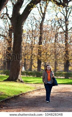 Beautiful young woman enjoying warm autumn day in park