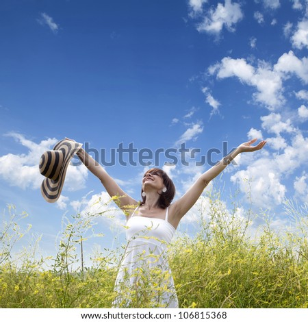 beautiful young woman enjoys a sunny day in the field