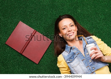 Beautiful young woman enjoys drinking coffee and lying on the grass.Woman drinking coffee - stock photo