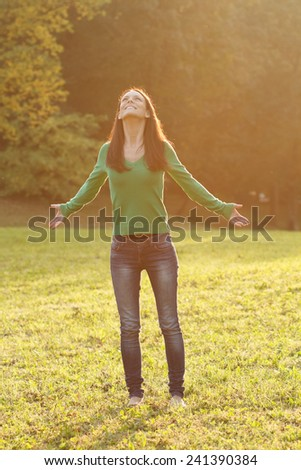 Beautiful young woman enjoys in nature.Peace of mind in nature - stock photo