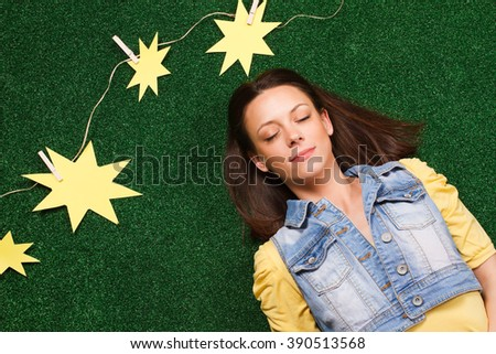 Beautiful young woman enjoys lying on the grass with lot of paper sun beside her.Happiness - stock photo