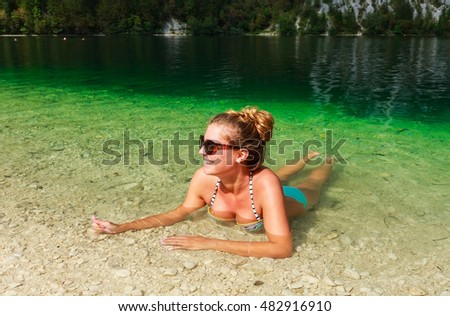 Beautiful young woman enjoys swimming and relaxing in natural green lake in summertime