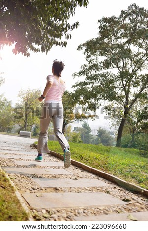 Beautiful young woman exercise jogging and runing on Park Road - stock photo