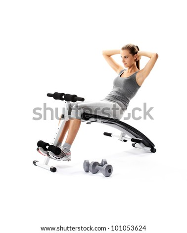 beautiful young Woman exercising abdomen muscles on bench - stock photo