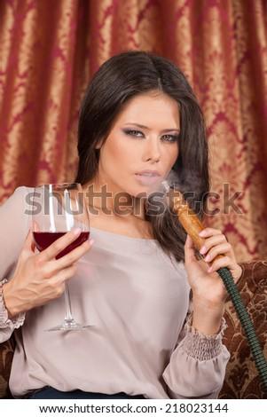 Beautiful young woman exhaling hookah. girl smoking turkish shisha and drinking - stock photo