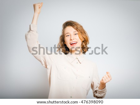 beautiful young woman exults the victory, close-up, isolated on a gray background