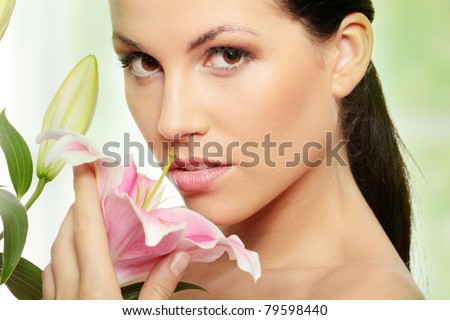 Beautiful young woman face with perfect skin with lily flower.