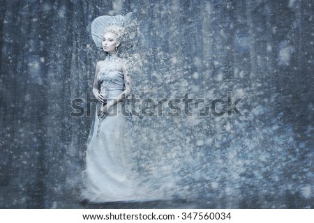 Beautiful young woman. Fairy tale snow queen in silver dress and crown with staff in magic forest. Copy space. - stock photo