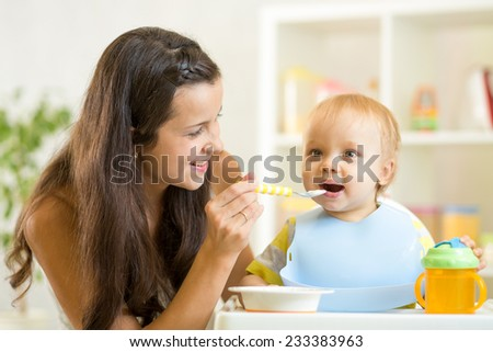 Beautiful young woman feeds son baby at home