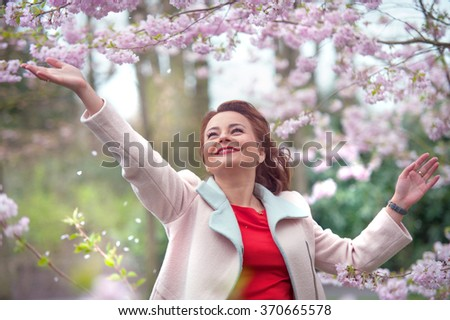 Beautiful young woman feeling happy in spring garden - stock photo