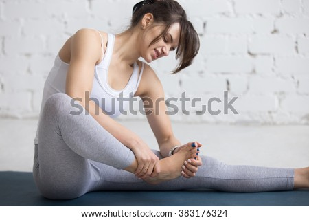 Beautiful young woman feeling pain in her foot during sport workout indoors, close-up,  focus on hands - stock photo