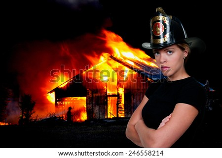 Beautiful young woman firefighter at a fire - stock photo