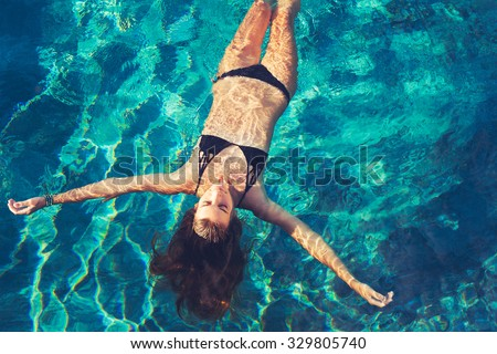Beautiful young woman floating in pool relaxing - stock photo