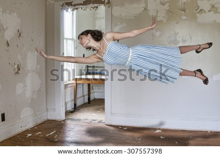 Beautiful young woman floating in the air - stock photo