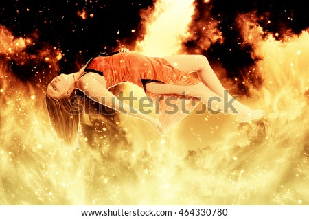 Beautiful young woman floating in the air on fire