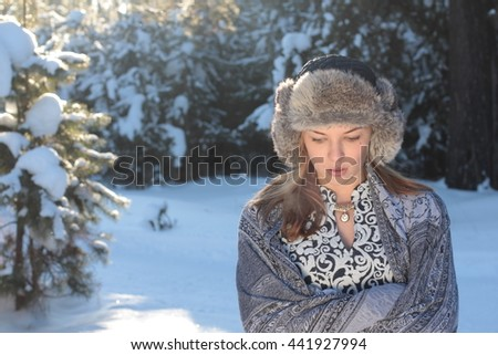 beautiful young woman freezes in the winter pine forest - stock photo