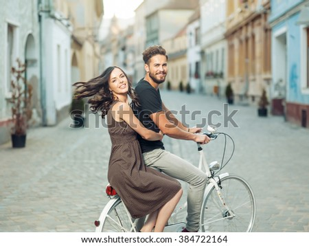 Beautiful young woman friend's bike , taking the mid , turns to smile at the camera on the move through town - stock photo