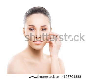 Beautiful young woman gently touching her face - stock photo