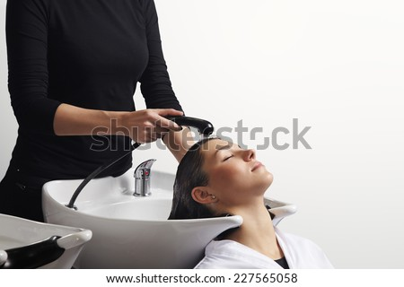 beautiful young woman getting a hair washed by hairdresser at salon - stock photo