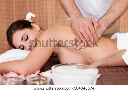 Beautiful young woman getting back massage at spa - stock photo