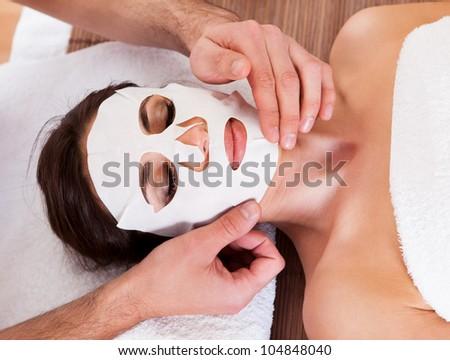 Beautiful young woman getting facial mask at spa studio - stock photo