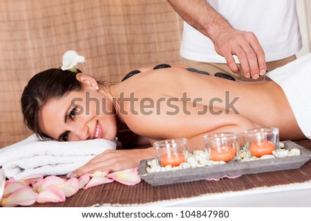 Beautiful young woman getting hot stone therapy at spa salon - stock photo