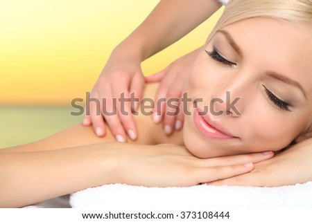 Beautiful young woman getting massage in spa salon - stock photo