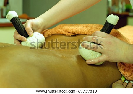 beautiful young woman getting massage with herbal stamps at spa