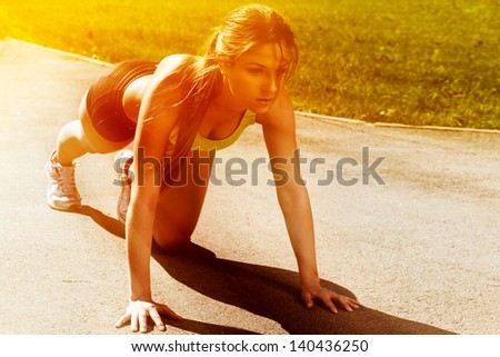 Beautiful young woman getting ready to run from lying pose - stock photo