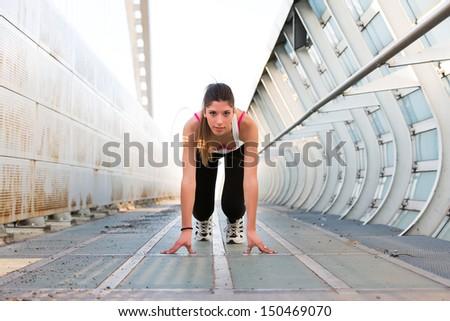 Beautiful young woman getting ready to run on a modern bridge - stock photo