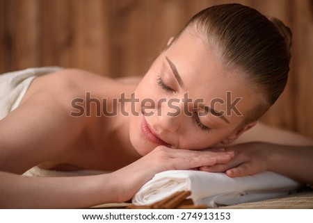 Beautiful young woman getting relaxing in the spa salon. Front view high resolution shot. Smiling model with closed eyes