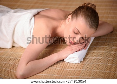 Beautiful young woman getting relaxing in the spa salon. Top view high resolution shot. Smiling model with closed eyes - stock photo