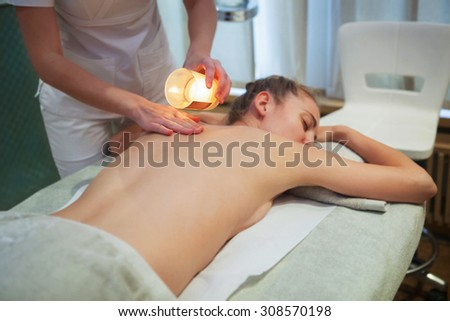 Beautiful young woman getting spa massage with massage candle - stock photo