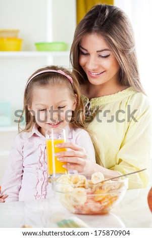 Beautiful young woman gives to the little girl orange juice and fruit salad in the kitchen. - stock photo