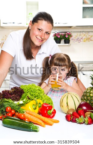 Beautiful young woman gives to the little girl orange juice  in the kitchen. - stock photo