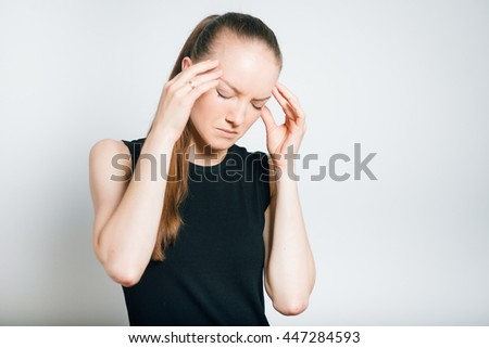 beautiful young woman has a headache, isolated on a gray background