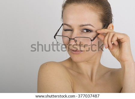 beautiful young woman has many different emotions, she winks. woman is wearing only glasses