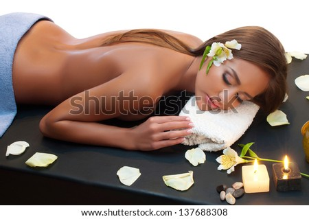 Beautiful young woman having a massage in a spa - stock photo